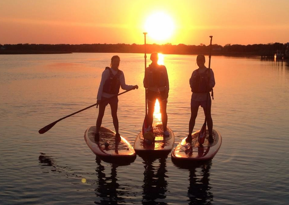 three paddlers in front of sunset